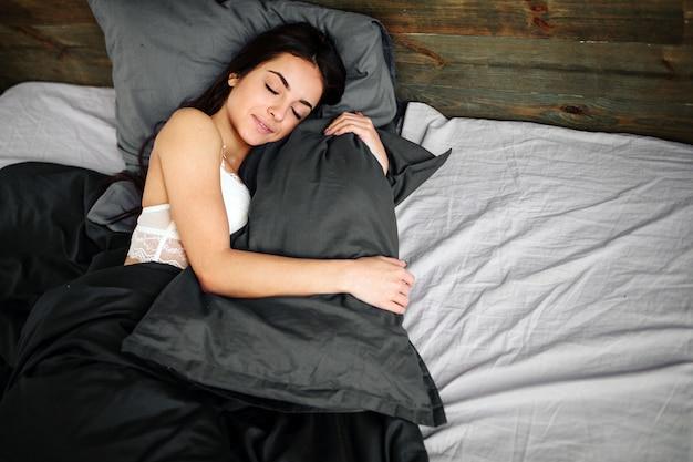 Vista lateral da bela jovem sorrindo enquanto dorme em sua cama em casa