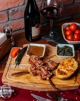 Vista lateral da carne de frango grelhado em palitos de madeira com batata assada e molho em uma placa de madeira