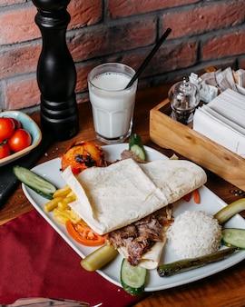 Vista lateral da carne doner com batatas fritas arroz e legumes no prato