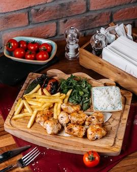 Vista lateral da carne grelhada de frango e legumes com batatas fritas em uma placa de madeira