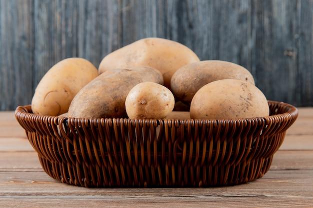 Vista lateral da cesta cheia de batatas inteiras na superfície de madeira e fundo com espaço de cópia