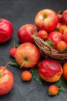 Vista lateral da cesta de frutas com maçãs, cerejas, folhas, nectarina, romãs