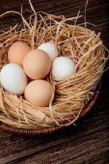 Vista lateral da cesta de ovos no ninho em fundo de madeira