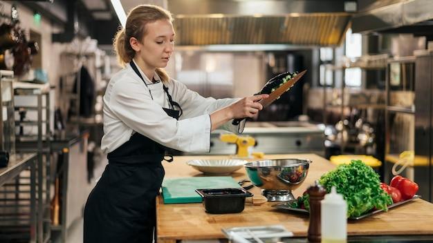 Vista lateral da chef feminina com avental cozinhando na cozinha