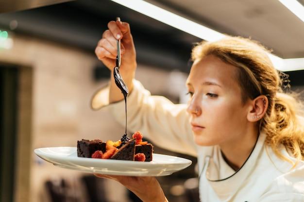 Vista lateral da chef feminina servindo molho sobre o prato