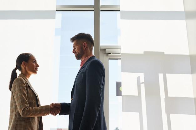 Vista lateral da cintura para cima em dois executivos modernos, homem e mulher, apertando as mãos