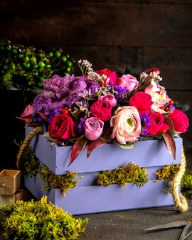 Vista lateral da composição de flores rosas cor de rosa e lilás em caixa de madeira