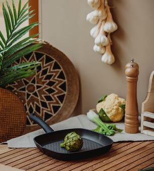 Vista lateral da couve de bruxelas verde islated em uma panela sobre uma mesa de madeira