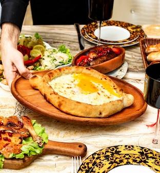 Vista lateral da cozinha georgiana tradicional khachapuri adjara com queijo e ovo de enchimento na bandeja de madeira