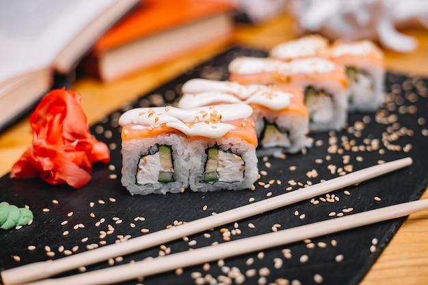 Vista lateral da cozinha japonesa tradicional filadélfia sushi roll com salmão filadélfia queijo pepino abacate em uma placa preta