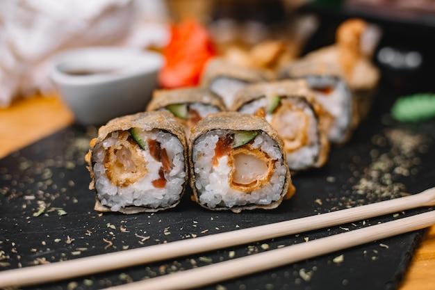 Vista lateral da cozinha japonesa tradicional sushi quente tempura de rolo com rei pepinos de camarão e cream cheese em uma placa preta