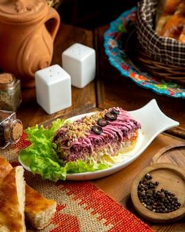 Vista lateral da cozinha tradicional russa, vestido camadas de salada de arenque de legumes cozidos em um prato branco em cima da mesa