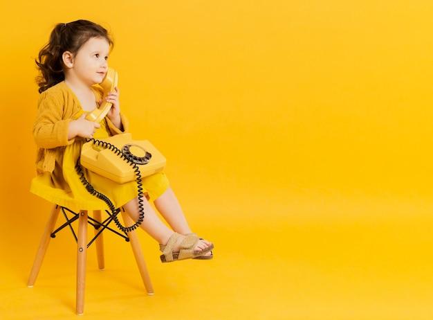 Vista lateral da criança adorável posando com telefone
