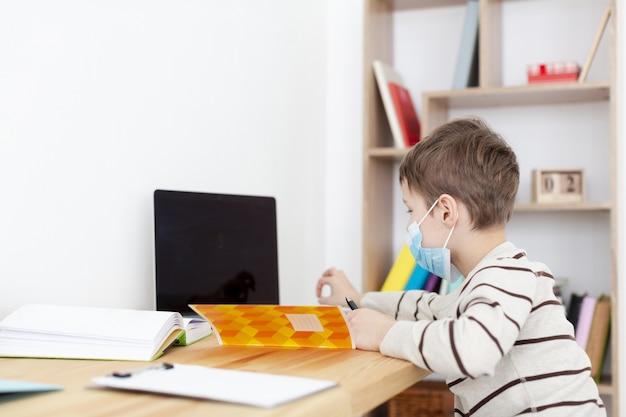 Vista lateral da criança com máscara médica fazendo lição de casa