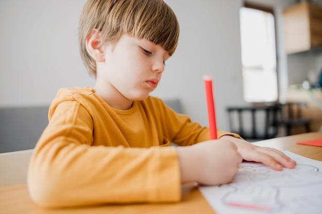 Vista lateral da criança desenhando em casa