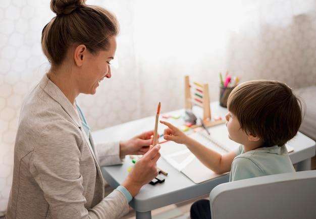 Vista lateral da criança e do tutor em casa aprendendo
