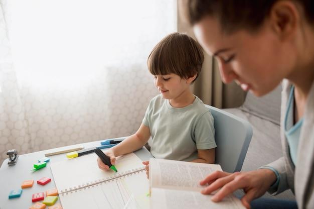Vista lateral da criança e tutor em casa