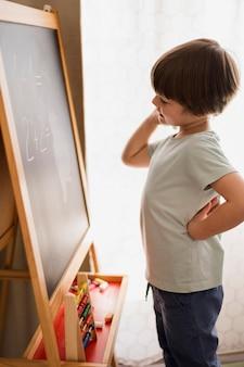 Vista lateral da criança em casa, resolvendo problemas matemáticos