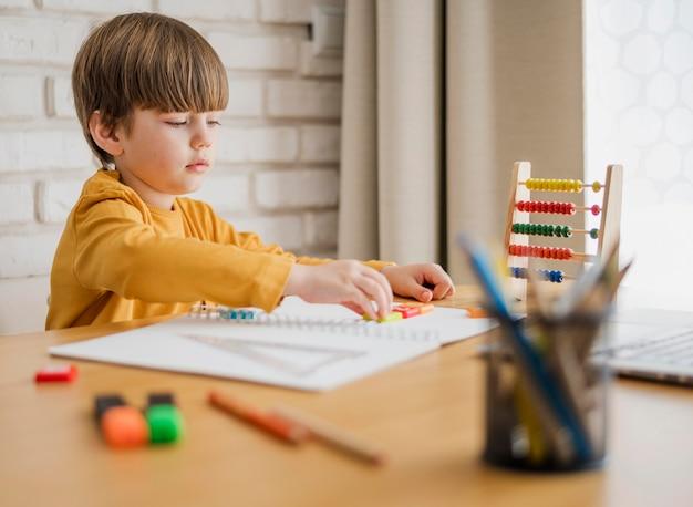 Vista lateral da criança em casa sendo orientada pelo laptop