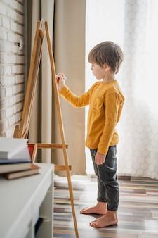 Vista lateral da criança escrevendo no quadro branco
