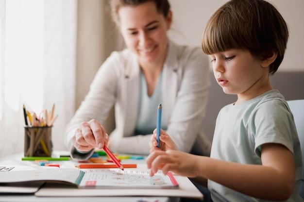 Vista lateral da criança estudando em casa com a ajuda do tutor