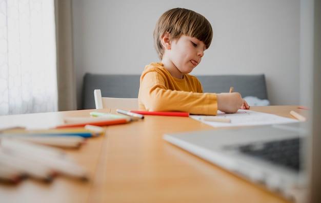 Vista lateral da criança na mesa de desenho