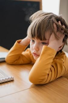 Vista lateral da criança na mesa estudando