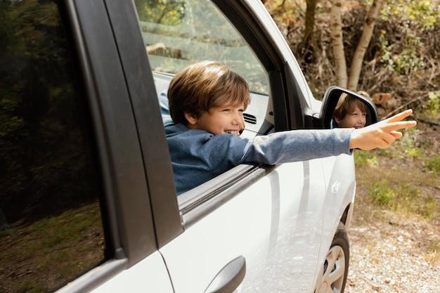 Vista lateral da criança no carro com os braços mostrando o símbolo da paz