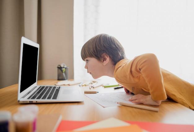 Vista lateral da criança olhando para laptop enquanto aprende em casa