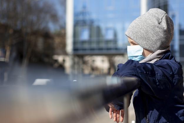 Vista lateral da criança vestindo máscara médica lá fora
