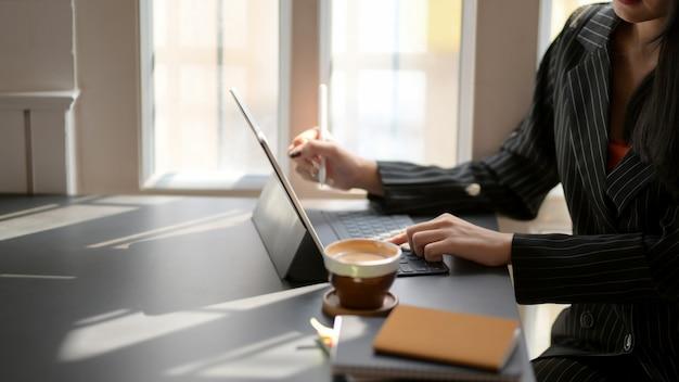 Vista lateral da digitação feminina no tablet digital na mesa preta em local de trabalho confortável