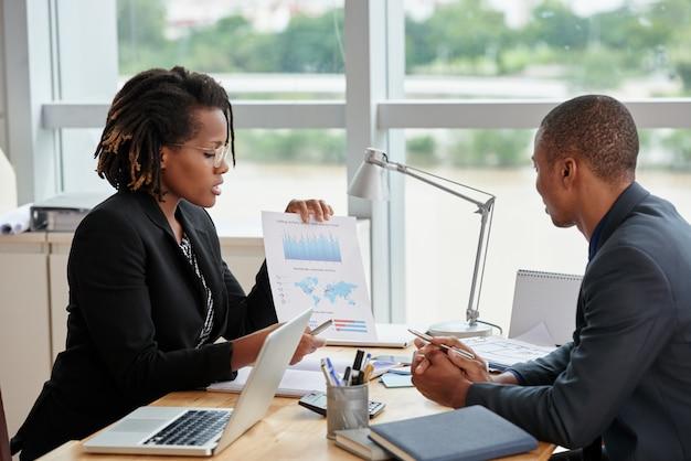 Vista lateral da empresária mostrando gráficos analíticos para seu colega de trabalho masculino