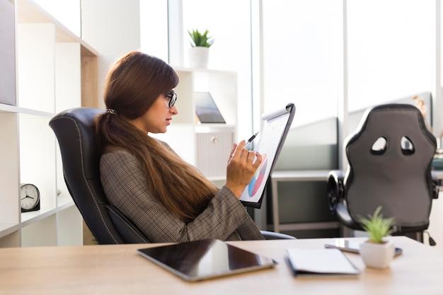 Vista lateral da empresária na mesa com o bloco de notas