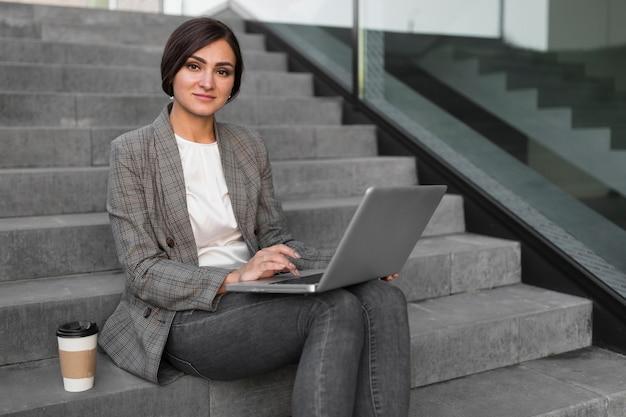 Vista lateral da empresária tomando café e trabalhando no laptop nas escadas