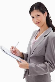 Vista lateral da empresária tomando notas