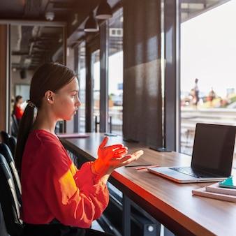 Vista lateral da empresária usando linguagem de sinais durante a videochamada