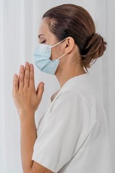 Vista lateral da enfermeira com máscara médica rezando