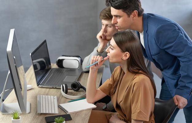 Vista lateral da equipe de profissionais trabalhando com computador e laptop