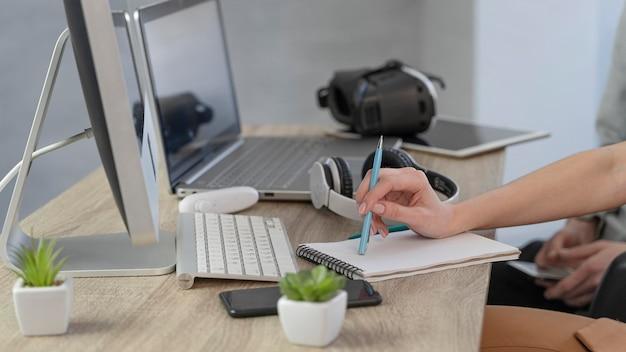 Vista lateral da equipe de profissionais trabalhando no computador e laptop