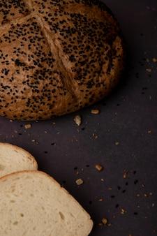 Vista lateral da espiga semeada com pão branco fatiado em fundo marrom com espaço de cópia
