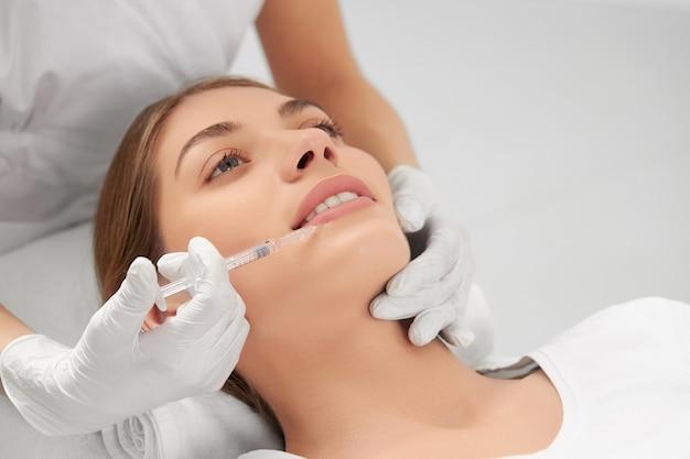 Vista lateral da esteticista com luvas de borracha brancas segurando uma seringa e aplicando injeção para aumento dos lábios