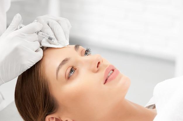 Vista lateral da esteticista com luvas de borracha brancas segurando uma seringa e aplicando uma injeção de beleza especial na pele do rosto