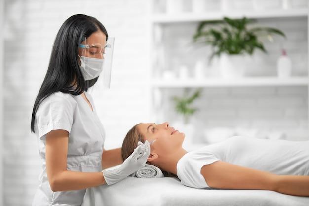 Vista lateral da esteticista morena com máscara protetora fazendo injeção de beleza para melhorar a pele do rosto