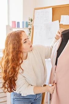 Vista lateral da estilista trabalhando no ateliê com forma de vestido