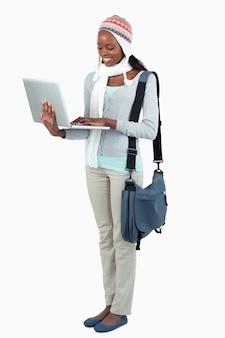 Vista lateral da estudante feminina com laptop e roupas de inverno