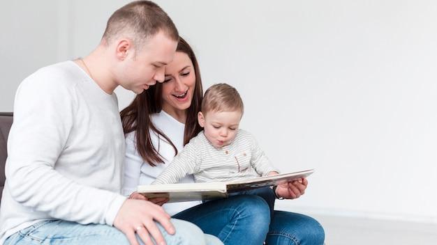 Vista lateral da família com criança e livro