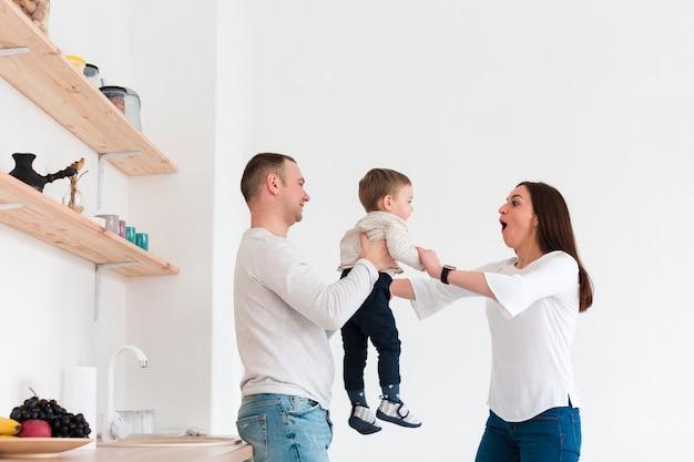 Vista lateral da família feliz com criança na cozinha