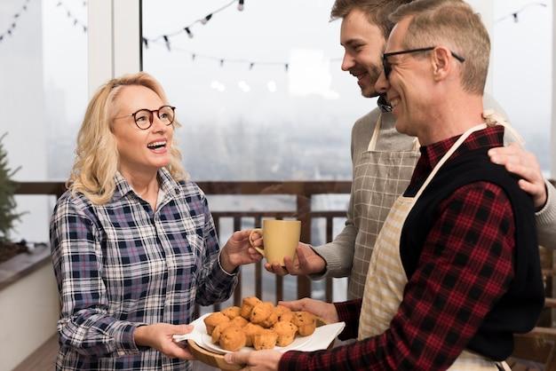 Vista lateral da família sorridente com muffins