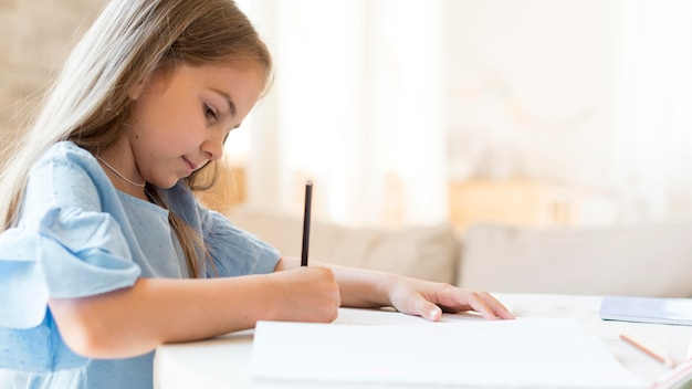 Vista lateral da filha fazendo a lição de casa em casa