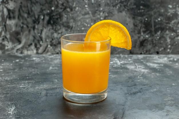 Vista lateral da fonte de vitamina suco natural fresco em fundo cinza